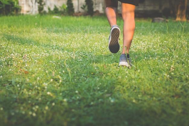 Avvicinamento. gamba. l'uomo con il corridore per strada sta correndo per l'esercizio. prato del corridore del bordo