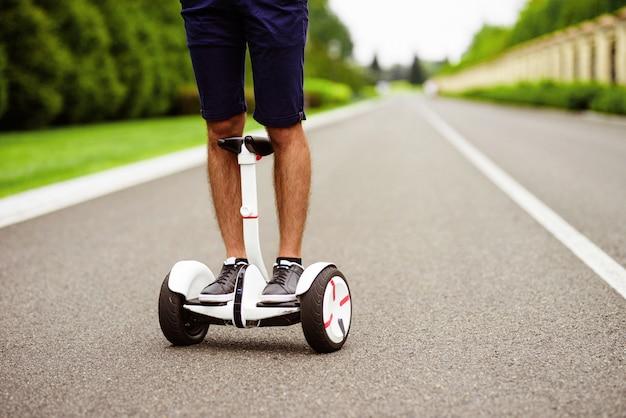Avvicinamento. gambe da uomo in scarpe da ginnastica grigie su un giroscopio.