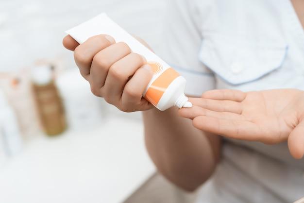 Avvicinamento. il medico mette sulle mani una crema speciale per il massaggio.