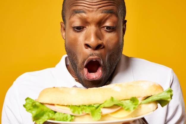 Avvicinamento. l'uomo di colore emozionante tiene il grande panino.