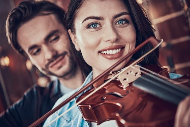 Avvicinamento. la ragazza suona il violino in negozio di strumenti musicali.