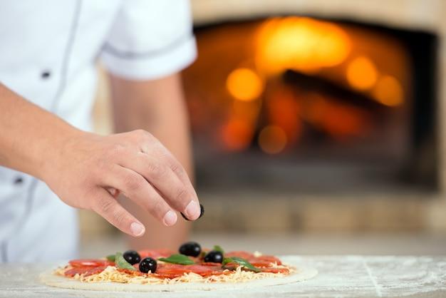 Avvicinamento. mano del panettiere del cuoco unico in uniforme bianca che produce pizza.