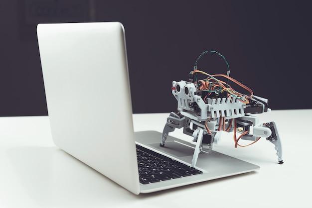 Avvicinamento. piccolo robot grigio con computer portatile sul tavolo.