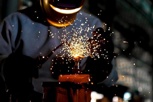 Avvicinamento. saldatore del lavoratore che lavora l'acciaio del gas della saldatura nell'industria con i guanti della maschera di sicurezza e le attrezzature di sicurezza.
