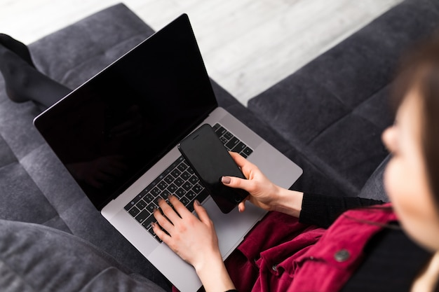 Avvicinamento. telefono e computer portatile usando abbastanza castana a casa nel salone