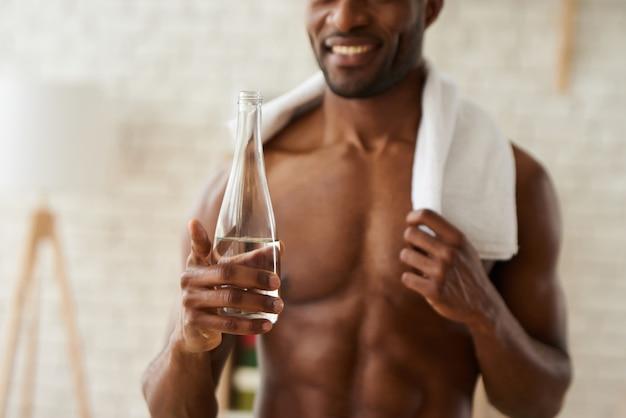 Avvicinamento. uomo africano con asciugamano e una bottiglia di succo.
