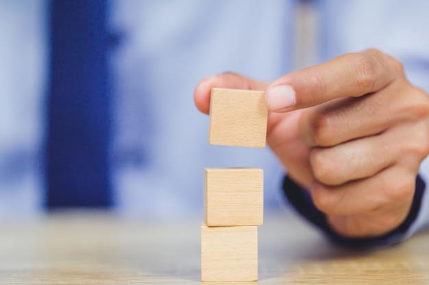 Avvicinati le mani di uomini d'affari, impilando blocchi di legno in gradini