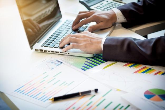 Avvio del processo di lavoro. uomo d'affari che lavora al tavolo di legno con il nuovo progetto di finanza. notebook moderno sul tavolo. punta di mano della penna