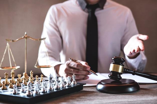 Avvocati maschi professionisti che lavorano all'aula di tribunale che si siede al tavolo e che firma le carte con il martelletto
