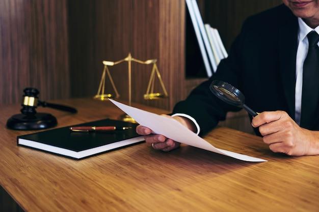 Avvocato che legge il contratto contrattuale e che esamina i documenti con la lente d'ingrandimento