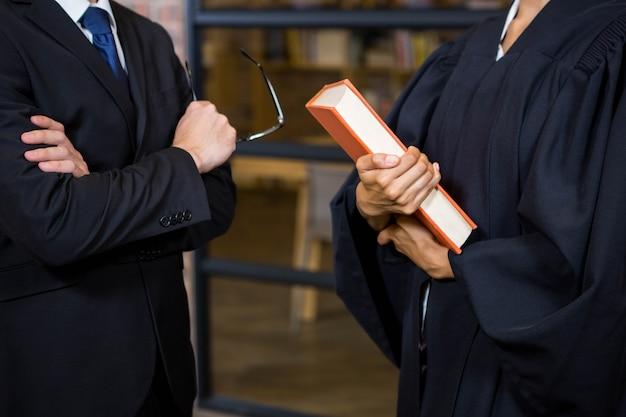 Avvocato che tiene un libro di legge in ufficio