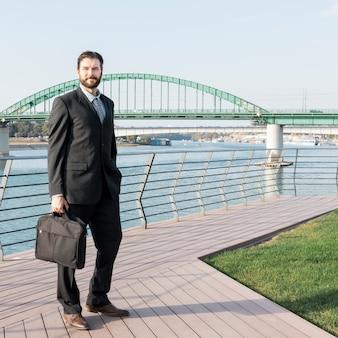 Avvocato con valigetta vicino al fiume