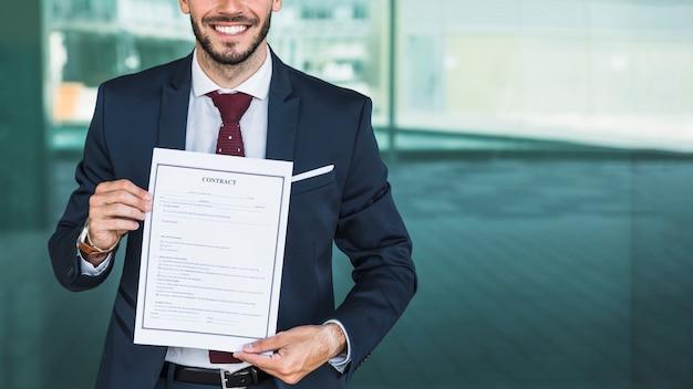 Avvocato di smiley del primo piano che tiene un contratto
