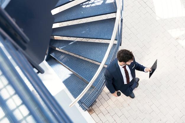 Avvocato di vista superiore che sta con la compressa vicino alle scale