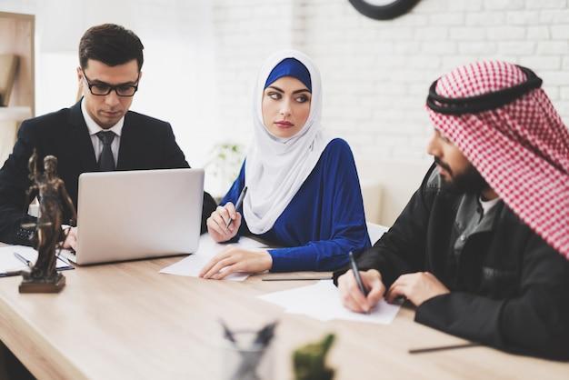 Avvocato in ufficio con marito e moglie arabi.