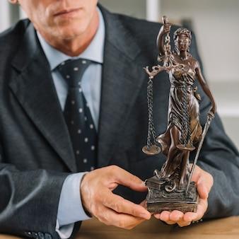 Avvocato maschio che giudica la statua di giustizia a disposizione