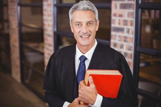Avvocato maschio che sta con il libro rosso all'ufficio
