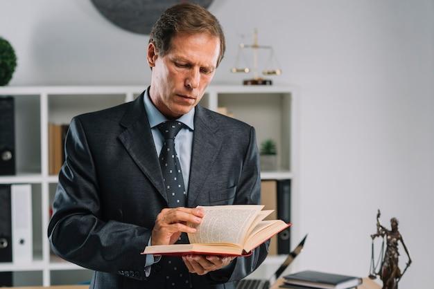 Avvocato maturo che gira le pagine del libro di legge nell'aula di tribunale