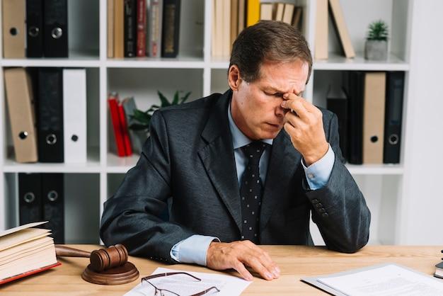 Avvocato maturo stanco che si siede nell'aula di tribunale