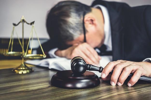 Avvocato o avvocato maschio è stanco ed emicrania durante il duro lavoro su un documento