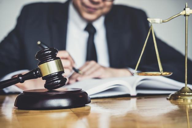 Avvocato o giudice che lavora con documenti contrattuali, libri di giurisprudenza e martelletto di legno sul tavolo in aula