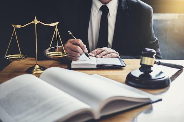 Avvocato o giudice che lavora con documenti contrattuali, libri di giurisprudenza e martelletto di legno sul tavolo
