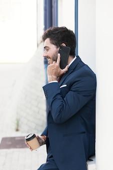 Avvocato vista laterale con caffè al telefono