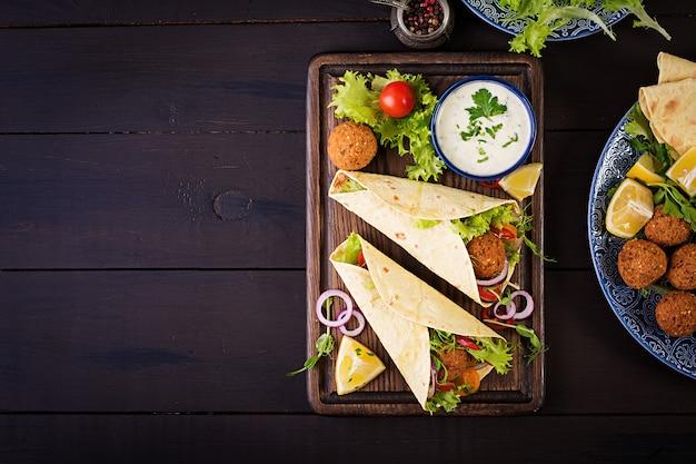 Avvolgere la tortilla con falafel e insalata fresca. tacos vegani. cibo vegetariano sano. vista dall'alto