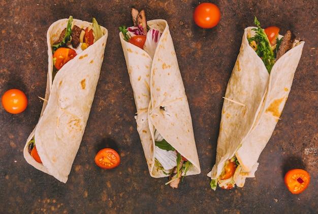 Avvolgere tacos di manzo messicano con pomodori su sfondo arrugginito