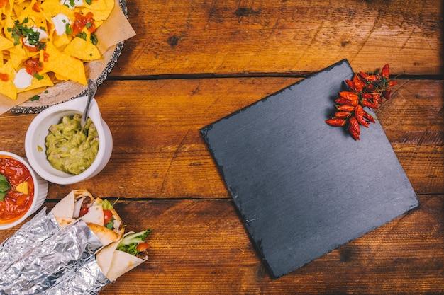 Avvolgi i tacos messicani; gustosi nachos; salsa di salsa; guacamole; ardesia nera e peperoncini rossi sul tavolo di legno marrone