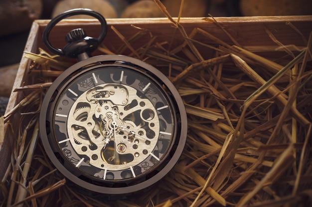 Avvolgitore per orologio da tasca su paglia di grano naturale in una scatola di legno.
