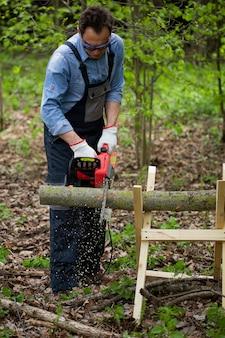 Axeman del taglialegna nel tronco di albero di taglio uniforme funzionante sul cavalletto con la motosega