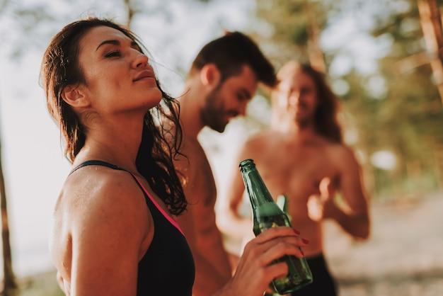 Azienda di adolescenti che beve birra sulla spiaggia.