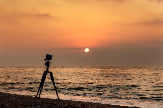 Azione fotocamera su un treppiede su una spiaggia sabbiosa che riprende un video del tramonto sul mare.