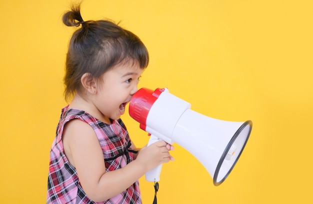Azione sveglia del megafono della tenuta della bambina per le insegne di promozione e del sito web.