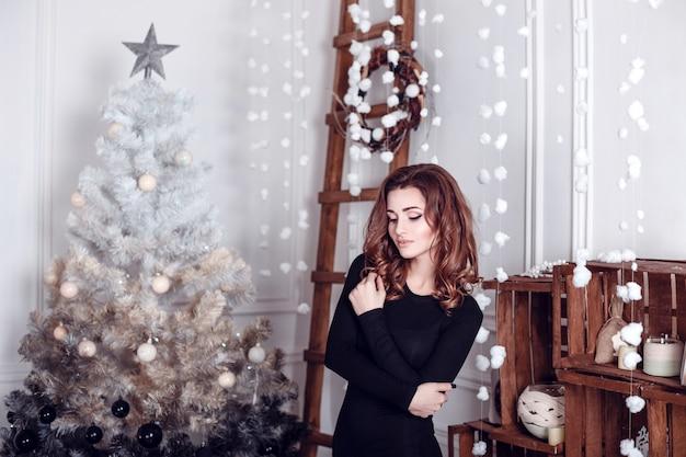 Babbo natale. bello modello sorridente della donna. trucco. stile di capelli lunghi e sani. elegante signora in abito nero su sfondo di luci albero di natale. felice anno nuovo