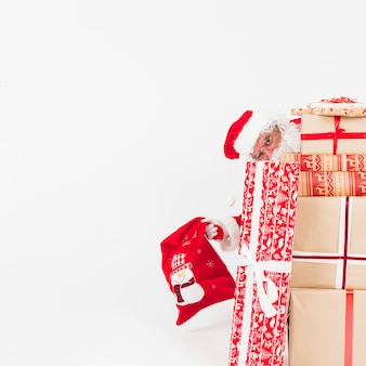 Babbo natale che fa capolino dalle scatole regalo
