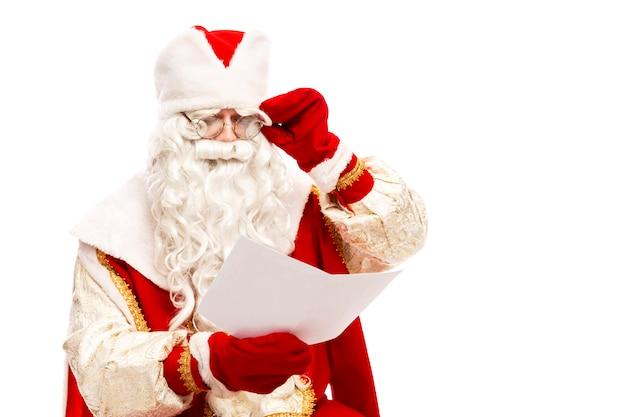 Babbo natale con gli occhiali che legge una lettera di desiderio con un elenco di regali. isolato su uno sfondo bianco.