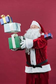 Babbo natale con scatole regalo colorate nelle mani