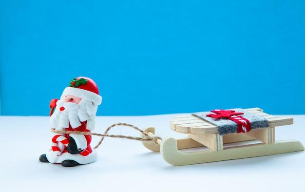 Babbo natale con slitta su uno sfondo azzurro, atmosfera natalizia, concetto di vacanze di capodanno