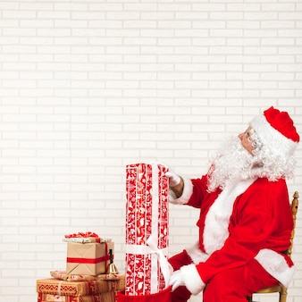 Babbo natale mettendo regali in borsa