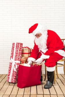 Babbo natale seduto e mettendo regali in un sacchetto di carta
