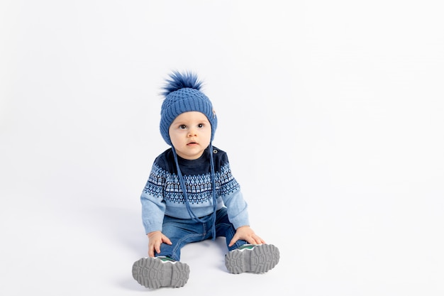 Baby 8 mesi ragazzo seduto su un muro bianco isolato in caldi abiti invernali e un cappello, moda per bambini, pubblicità abbigliamento per bambini,