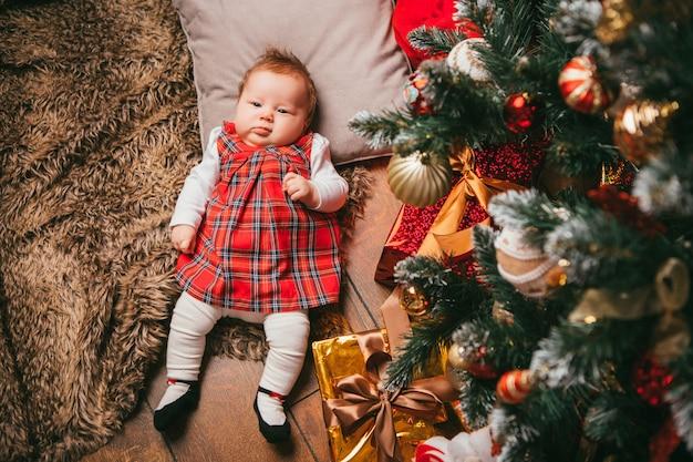 Baby accanto all'albero di natale
