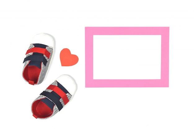 Baby scarpe per bambini e cornice rosa su bianco.