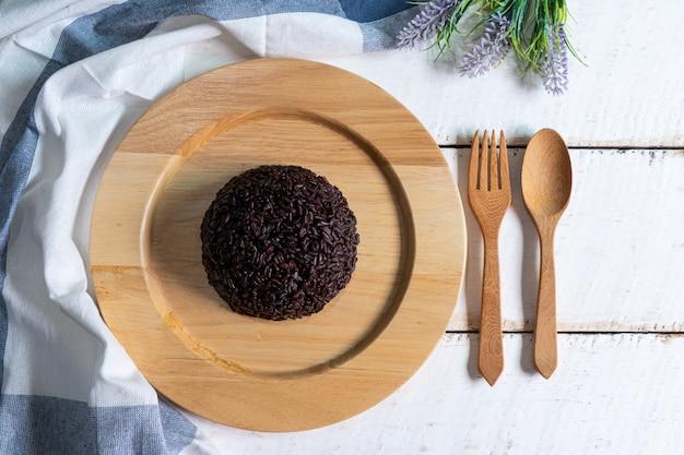 Bacca del riso cotta a vapore in piatto di legno su fondo di legno bianco