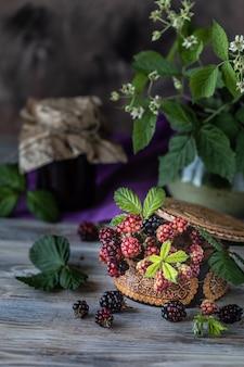 Bacca di blackberry su un ramo con foglie in una scatola di legno intagliato su un legno scuro