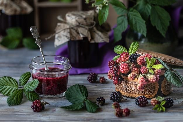 Bacca di blackberry su un ramo con foglie in una scatola di legno intagliato su uno sfondo di legno scuro.