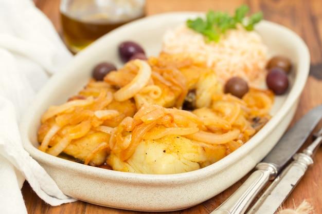 Baccalà fritto con riso e olio d'oliva bolliti sul piatto
