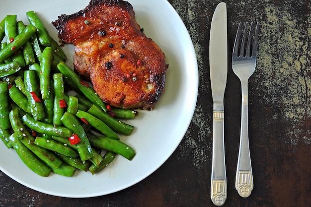 Baccelli di pisello e bistecca di maiale su un piatto. dieta keto.